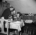 Echtpaar aan tafel in de woonkamer de man reikt zijn vrouw een glaasje aan, Bestanddeelnr 252-9337.jpg