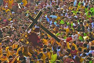 Black Nazarene - Marshals in yellow lift the Black Nazarene onto its ándas at the start of the Traslación. The peana or base of the image can be seen under the hem of its robes.