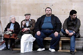 Obesity in the United Kingdom - Visitors sitting outside the British Museum in London including an obese man