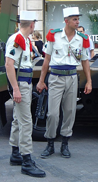 Legionnaires in modern dress uniform. Note the green and red epaulettes, the distinctive white kepi and the blue sash. They carry France's standard assault rifle, the FAMAS. French Foreign Legion dsc06878.jpg