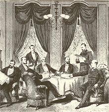 Dessin noir et blanc montrant des civils et des militaires, certains assis, d'autres debout, autour d'une table, examinant et discutant les documents objets du traité.