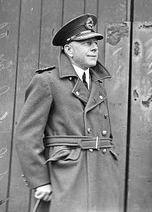 Three-quarter informal portrait of man in military overcoat and peaked cap, holding a cane
