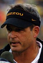"A headshot of a man with a microphone to his mouth wearing a black visor with the word ""MIZZOU"" in gold on the front."