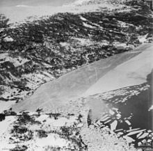 Two ships close to the shore of a body of water near steep snow-covered hills. Much of the body of water is covered by sheets of ice.
