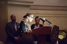 Ginsburg speaking at a podium