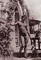 Gloeden, Wilhelm von (1856-1931) - n. 0692 - Vor einem Haus posierender Junge mit Stab und Blumenkrone (Zeno Fotografie).jpg