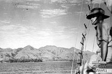 A man in a slouch hat looks out from a sailing ship over a mountainous coastline.