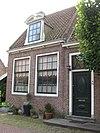 foto van L-vormig huis, in hoofdzaak. Twee ingangen met vroeg 19e-eeuwse deur en snijraam. Drie dakkapellen met gebogen doorbroken frontons. Inwendig vier gesneden laatgotische sleutelstukken