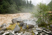 Steaming pool of water surrounded by a group of rocks next to a muddy river.