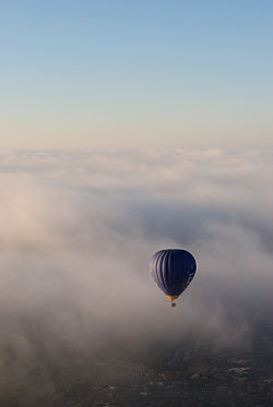 Hot air balloon rising above the clouds 2.JPG
