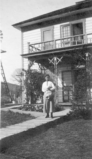 Boyd, Oregon - Boyd General Store proprietor James C. Greenlee's daughter, Alma, in front of their family home in town. Circa early 1900s. Courtesy Gilhousen Family Association.