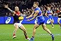 Jake Stringer handballing away from Nathan Jones.jpg