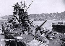A view over a dock containing a large warship in the final stages of construction. Hills and a town can be seen across the harbor, a number of other ships are visible in the middle distance, and filling the foreground the warship's deck is littered with cables and equipment.