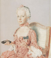 Solemn-faced girl child in a pink dress decorated with bows. Facing half-left, she carries an object in her right hand that might be a compact, or a mirror.