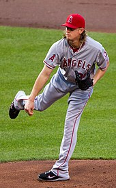 "Jered Weaver, wearing a red baseball cap and grey baseball uniform with the words ANGELS across and an ""A"" patch on the right sleeve, delivers a pitch"