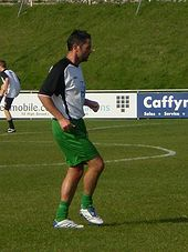 A dark-haired white man wearing sports kit exercising on a sports pitch with advertising boards and a grass bank in the background.