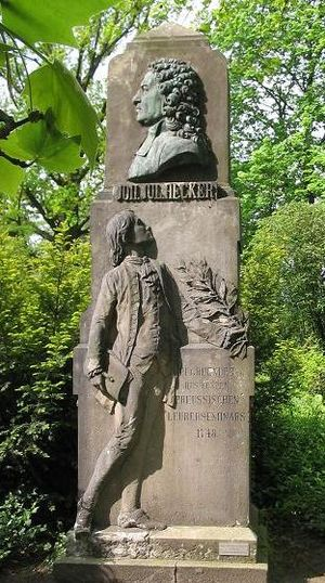 Prussian education system - Johann Julius Hecker memorial in Berlin honors him founding the first prussian teachers seminary in 1748, Heckers bust thrones over a future teacher in classical regalia and posture