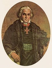 A painted half-length portrait of a white-haired man wearing a black mantle over a black tunic belted in green and with a large cross on a red ribbon about his neck