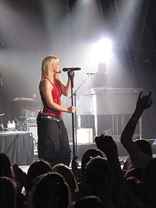 Right profile of a blond woman on a stage. She wears a red top and black trousers and sings in a hand-held microphone. The stage is lit by lights from above and a keyboard player is visible behind the woman. Also visible are the back-profiles of the audiences.