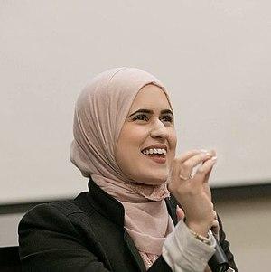 Laila Alawa sits with microphone