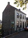 foto van Gepleisterde lijstgevel voor huis met hoog zadeldak