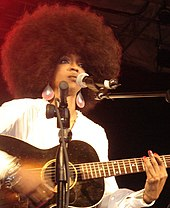 An African-American female with a black afro strumming on a guitar in front of a microphone.