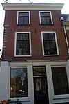 foto van Hoekpand met ontlastingsbogen boven de vensters in de verdieping. Pui uit de tweede helft 19e eeuw, houten kroonlijst