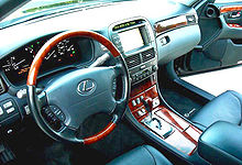 Automobile front interior, driver side, with dashboard navigation screen, wood steering wheel and console.