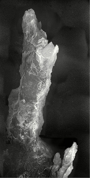 Lost City Hydrothermal Field - A carbonate chimney more than 9 meters (30 feet) in height. The white, sinuous spine is freshly deposited carbonate material. The top shows evidence of collapse and re-growth, as indicated by the small newly developed cone on its top.