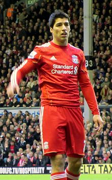 Luis Suárez - wearing a red Liverpool FC jersey with the Standard Chartered sponsor logo at the front centre and shorts with a number 7 partially obscured on the left-leg side and the club crest on the right - lifts his hand with his mouth partly opened.