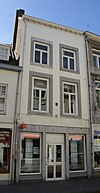 Huis met gepleisterde lijstgevel, voorzien van vensters in Naamse steen.