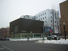 Modern building seen from across the street, cyclist out front, snow on the ground. Six story silver tower. Two story entrance. First floor is glass, second floor is high-ceilinged, dark solid with window in front.