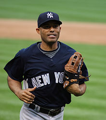 Mariano Rivera jogging on a baseball field wearing a baseball glove and navy blue hat and baseball jersey.