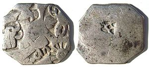 Silver punch mark coin of the Mauryan empire, with symbols of wheel and elephant. 3rd century BCE.
