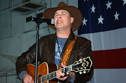 A middle-aged man in a cowboy hat and a leather jacket, playing a guitar and singing into a microphone in front of the American flag
