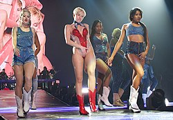 A short-haired blonde woman dressed in a sparkly red and white leotard is seen alongside three background dancers dressed in denim.