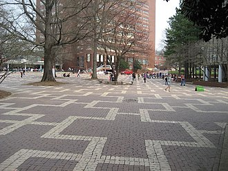 The Brickyard (NC State) - Students walking across the Brickyard with D.H. Hill Library in background