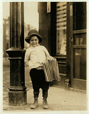 Eight year old newsboy in a black and white photograph with a bundle of newspapers under his arm