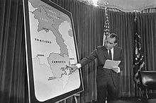 Nixon se tient devant une grande carte de l'Indochine et montre le Cambodge du doigt.