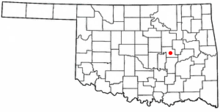 A white map of Oklahoma with a red dot in the center