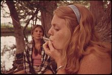 A young woman looking left with her eyes nearly closed smokes a large cigarette in a wooded setting near a body of water. Behind her another young woman looks at her