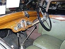 Photo de l'intérieur d'une voiture, la planche de bord est en bois et la sellerie de couleur verte.
