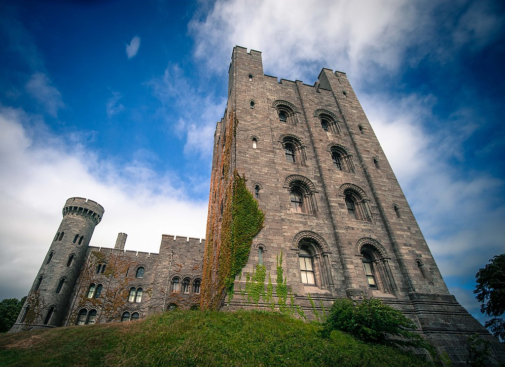 The exterior of Penrhyn Castle in wales with  plant life growing up the side of the walls