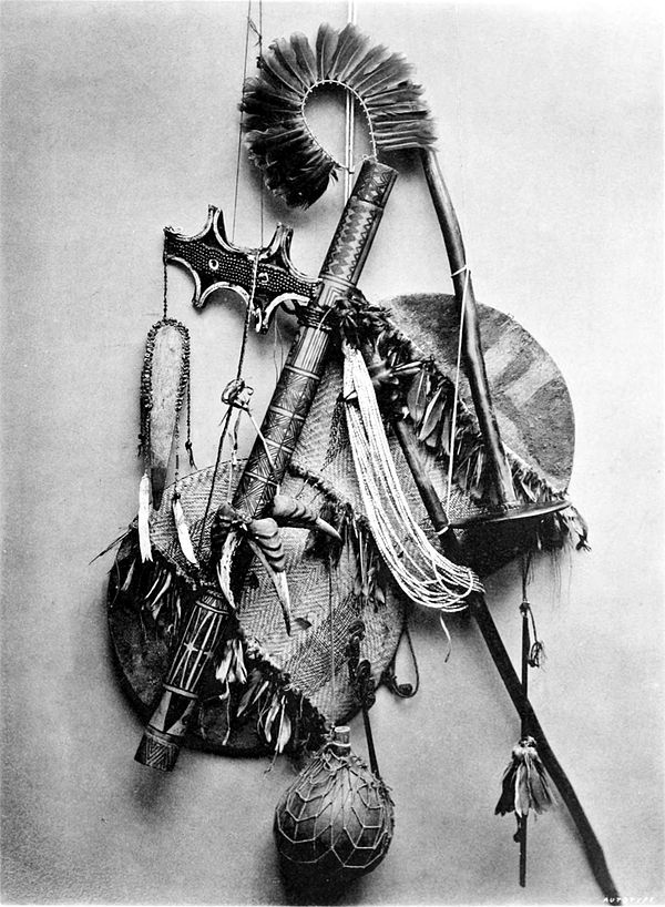 Black and white photograph of a collection of several implements.  Includes, feathered headdress, an axe-like weapon and circular objects.
