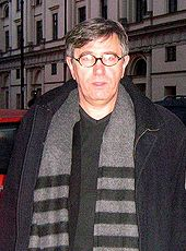 A middle-aged man with greying hair, wearing black-rimmed oval spectacles and a dark grey jacket and light grey and black striped scarf, photographed in the street