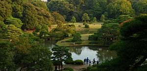 A panoramic view of the Rikugi-en Garden from the Fujishiro-toge hill vantage point. Green trees surround a serene lake.