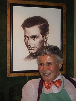 Vincent Fourcade - Robert Denning sitting in front of a portrait of Vincent Fourcade