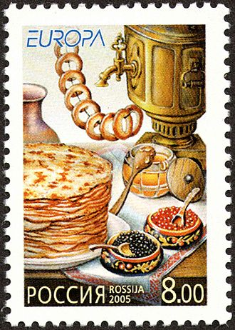 Russian cuisine - Russian postage stamp showing the typical delicacies served at Maslenitsa: bliny, caviar, bubliki, honey, and tea in a samovar