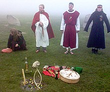 Four figures in medieval period costume stand outside on a grassy area. The image is misty.