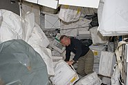 STS-135 Doug Hurley moves around supplies and equipment in the Leonardo PMM